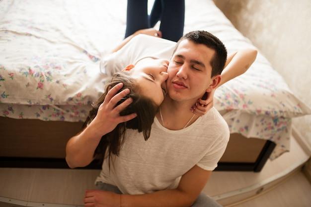 Un chico con una chica, besándose en la cama.