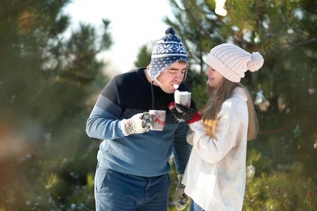Chico con chica en el bosque de invierno con una taza de bebida caliente
