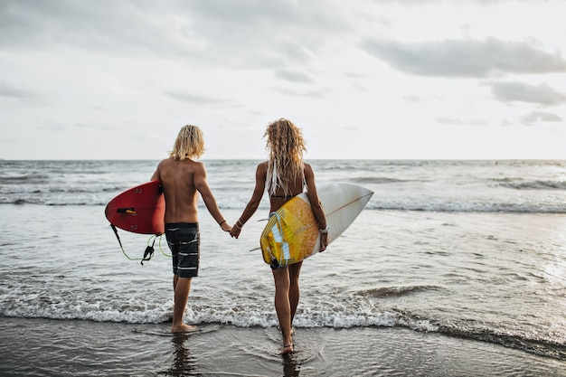Chico y chica con cabello ondulado van de la mano al mar y sostienen tablas de surf
