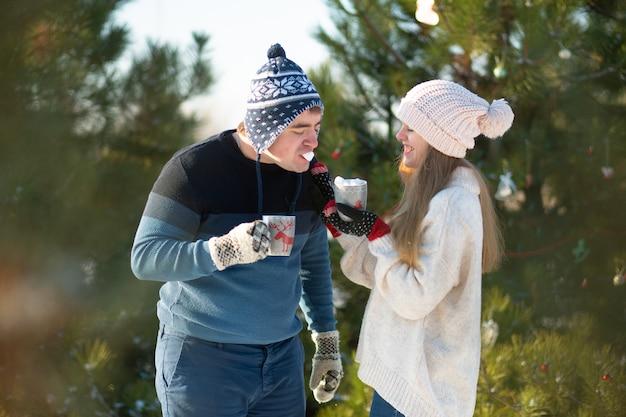El chico con la chica camina y se besa en el bosque de invierno con una taza de bebida caliente