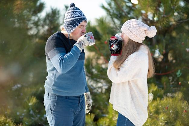 El chico con la chica camina y se besa en el bosque de invierno con una taza de bebida caliente.