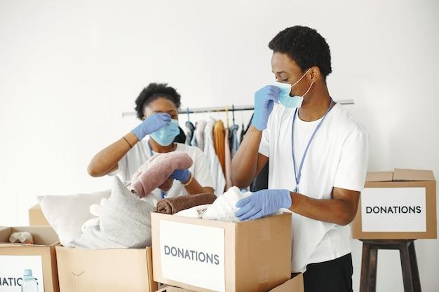 Chico y chica con casillas de verificación. voluntarios africanos con máscaras. cajas con ayuda humanitaria.