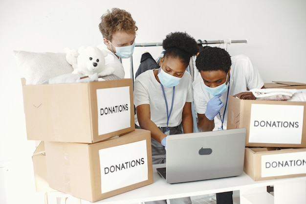 Chico y chica con casillas de verificación voluntarios enmascarados con portátil cajas con ayuda humanitaria
