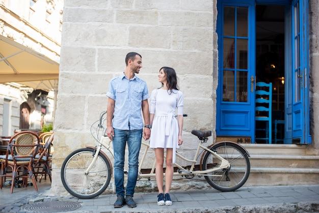 Chico y chica cerca de bicicleta tándem, paredes y puerta vintage