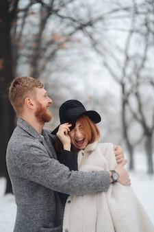 El chico y la chica descansan en el bosque de invierno.