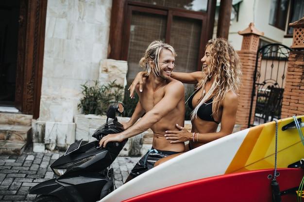Chico y chica esbeltos en trajes de baño se sientan en motocicleta con tablas de surf fijas