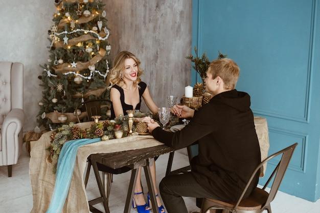 El chico y la chica están cenando en la mesa festiva. la mesa está decorada en estilo de año nuevo. rubia vestida de negro, con lápiz labial rojo en los labios. árbol de navidad decorado.