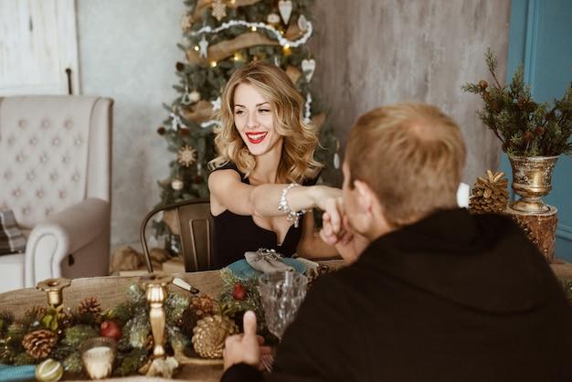 El chico y la chica están cenando en la mesa festiva. rubia vestida de negro, con lápiz labial rojo en los labios. cuchillería. pared azul. árbol de navidad decorado.