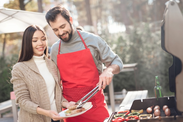 Un chico y una chica están cocinando comida de barbacoa durante un picnic.