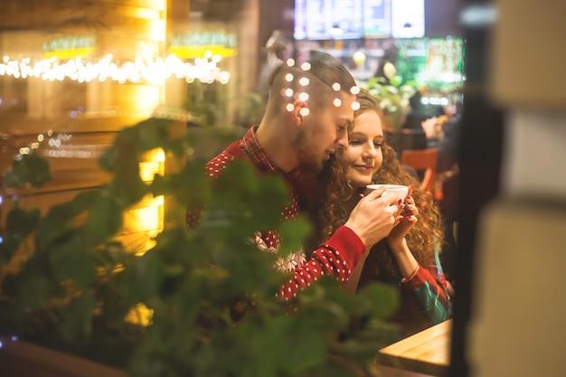 Un chico y una chica están sentados en un café junto a la ventana.