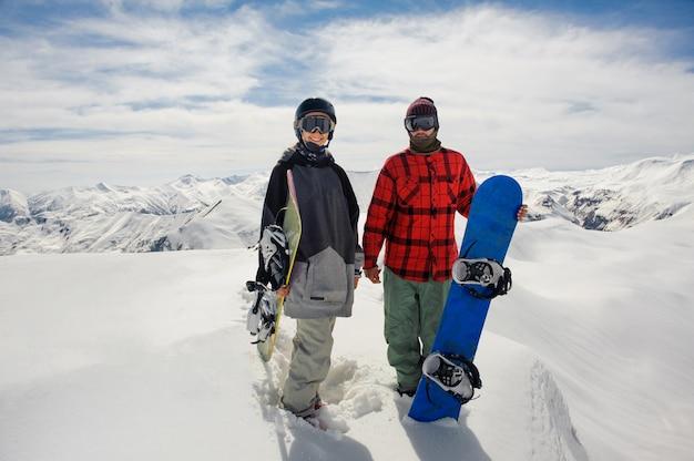 Chico y una chica con gafas de esquí están parados en la nieve con tablas de snowboard