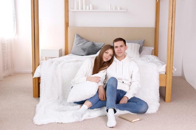 Chico y chica hermosa en el dormitorio con un libro junto a la cama de la casa