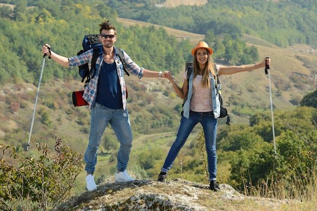 Chico y chica se paran en las montañas y se regocijan.