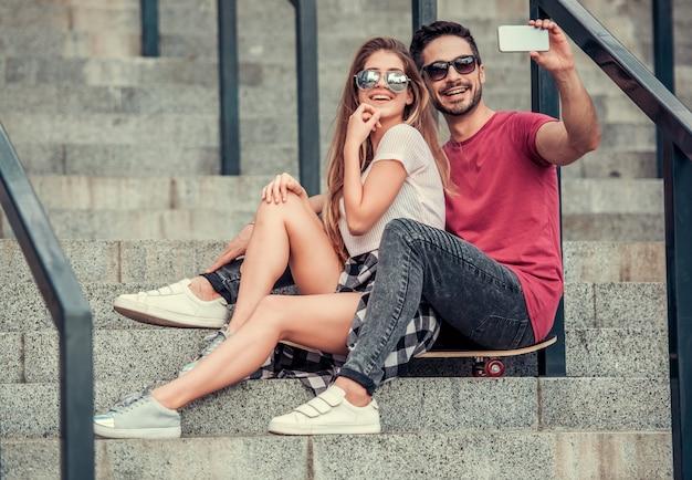 Chico con chica en pasos tomar selfie en teléfono y sonreír. pareja joven tomando selfie en teléfono mientras está sentado en patineta.