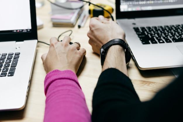 Chico y chica que trabajan en una oficina en portátiles, en un proyecto