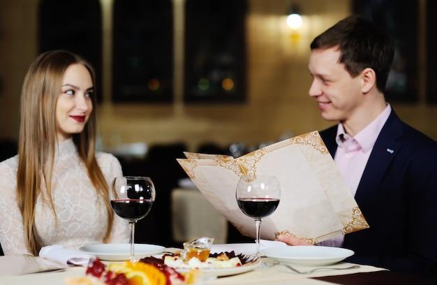 Chico con una chica en un restaurante elige platos del menú