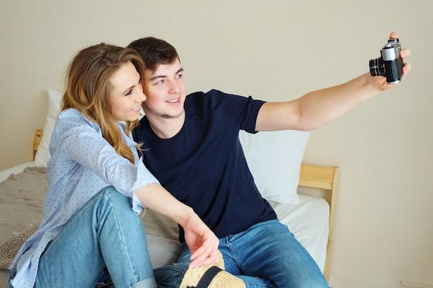 Chico chica sentarse en la cama hacer selfie con cámara vieja posando