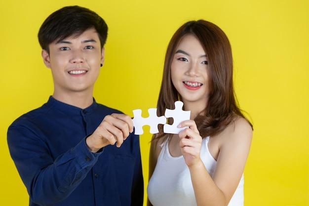 El chico y la chica sostienen piezas de rompecabezas en la pared amarilla