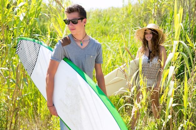 Chico y chica surfista caminando en la jungla verde