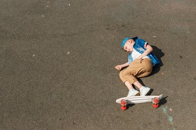 Un chico de ciudad pequeña y patineta. un chico joven está montando en una patineta parka