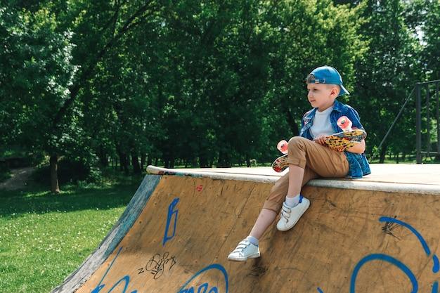 Un chico de ciudad pequeña y patineta. un chico joven está de pie en el parque y sosteniendo una patineta
