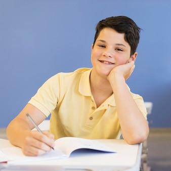 Chico en clase escribiendo