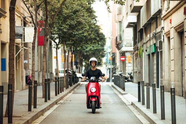 Chico conduciendo moto roja en barcelona
