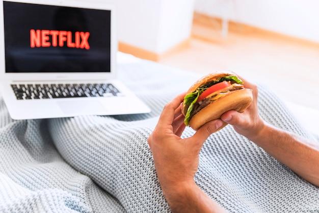 Chico de cultivo comiendo y viendo programas de netflix