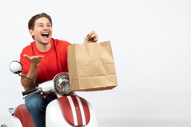 Chico curioso mensajero sonriente joven en uniforme rojo sentado en scooter sosteniendo una bolsa de papel en la pared blanca