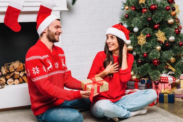 Chico dando presente a la señora cerca del árbol de navidad