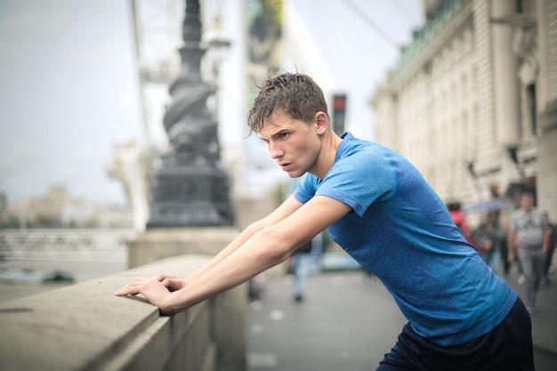 Chico deportivo guapo haciendo algunos ejercicios en la calle