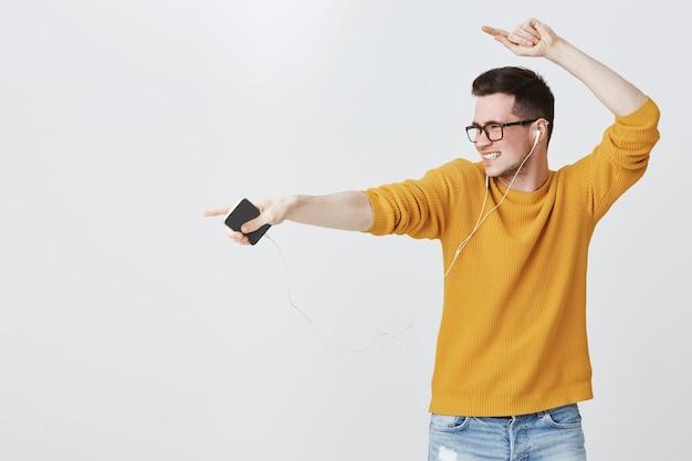 Chico despreocupado feliz bailando como escuchar música en auriculares, sosteniendo el teléfono móvil