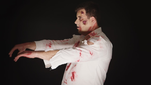 Chico disfrazado de zombi para halloween con sangre y cicatrices sobre fondo negro.
