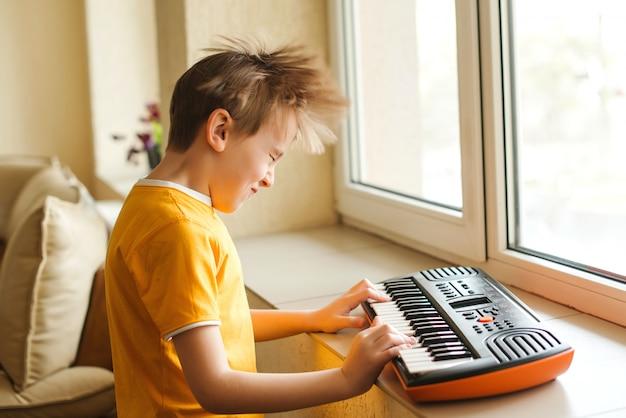 Chico divertido bailando mientras juega en sintetizador. piano infantil desarrollo de habilidades musicales en niños.