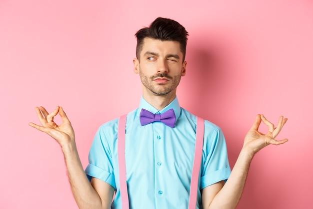 Chico divertido con bigote y pajarita falsa meditando, mirando a un lado mientras hace yoga asana, de pie sobre fondo rosa.