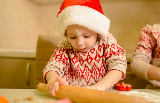 Chico divertido está horneando galletas de navidad