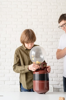 Chico divertido inflar un globo con helio