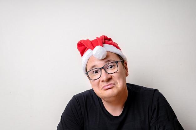 Chico divertido joven con sombrero de navidad en la pared blanca. triste santa navidad