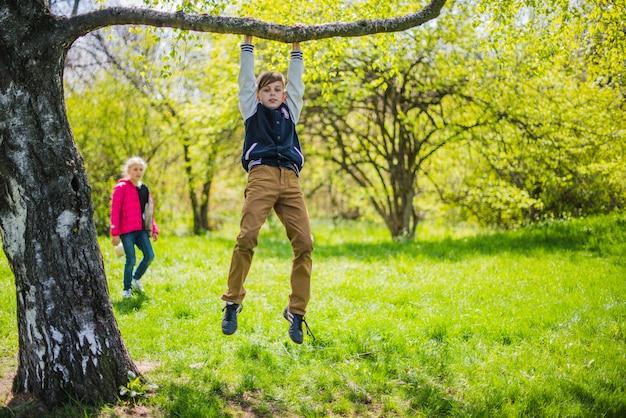 Chico divertido jugando en la rama de un árbol