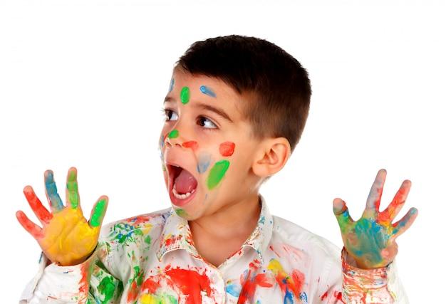 Chico divertido con las manos y la cara llena de pintura.