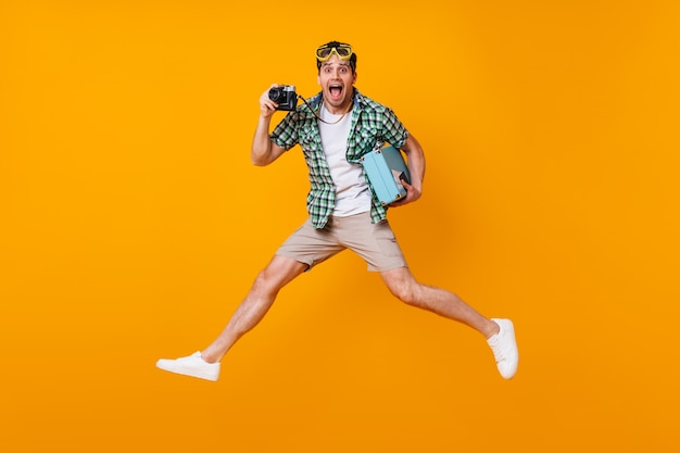 Chico divertido turista en traje de verano con cámara retro y maleta azul. hombre con máscara de buceo saltando sobre el espacio naranja.