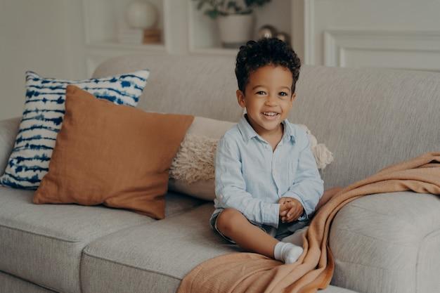 Chico dulce niño afro en ropa casual sentado en un cómodo sofá y jugando en el interior