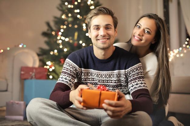 Chico dulce que le da a su novia su regalo de navidad para ella