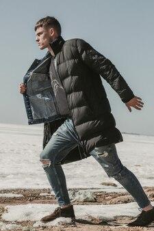 Chico elegante avanzando en la orilla del mar cubierto de nieve con un abrigo negro y jeans desaliñados.