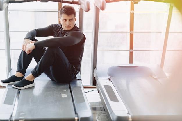Chico elegante en el gimnasio se sienta descansando en la cinta. estilo de vida saludable.