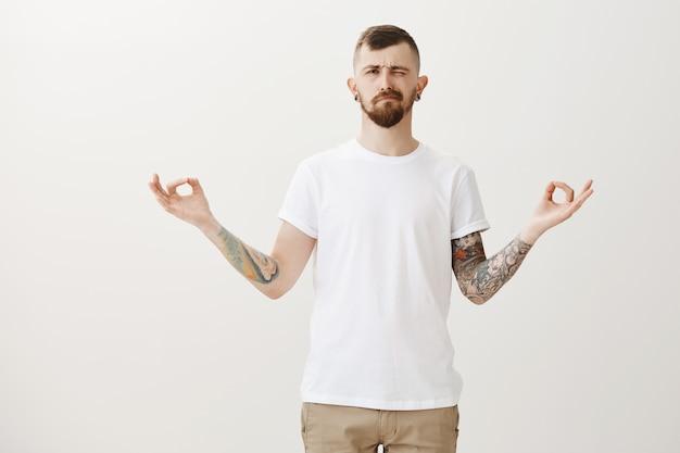 Chico elegante hipster tratando de meditar, mirando a la izquierda al molesto sonido