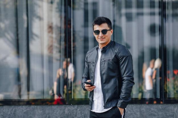Chico elegante joven con gafas en chaqueta de cuero negro con teléfono sobre fondo de cristal