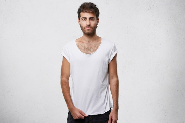Chico elegante mostrando su camiseta blanca vacía en blanco