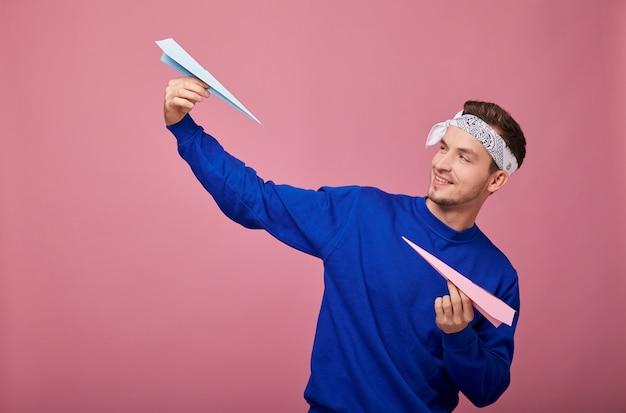 Chico elegante sonriente en suéter de bandanin está de pie con aviones de papel en la mano