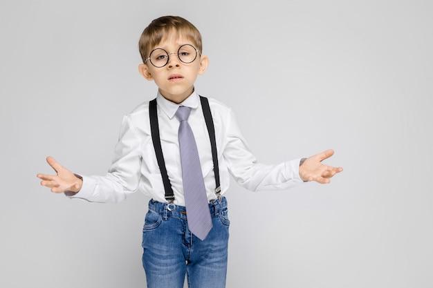 Un chico encantador con una camisa blanca, tirantes, una corbata y jeans ligeros está parado en gris